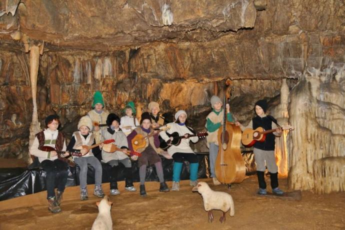 Tamburjaši igrajo na tamburice v sklopu živih jaslic v Postojnski jami